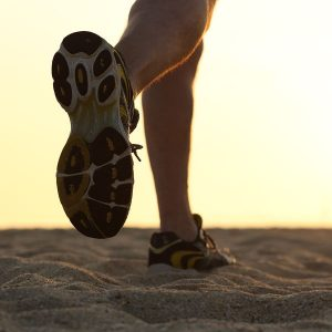 Legs and shoes of a man running at sunset with the horizon in the background